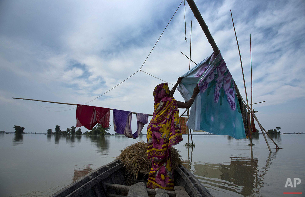 An Indian woman stands on a boat and hangs clothes to dry at flooded Sildubi village, in the northeastern Indian state of Assam, Friday, July 29, 2016. Torrential monsoon rains have caused widespread flooding in Assam state and forced around 1.2 million people to leave their water-logged homes. (AP Photo/Anupam Nath)