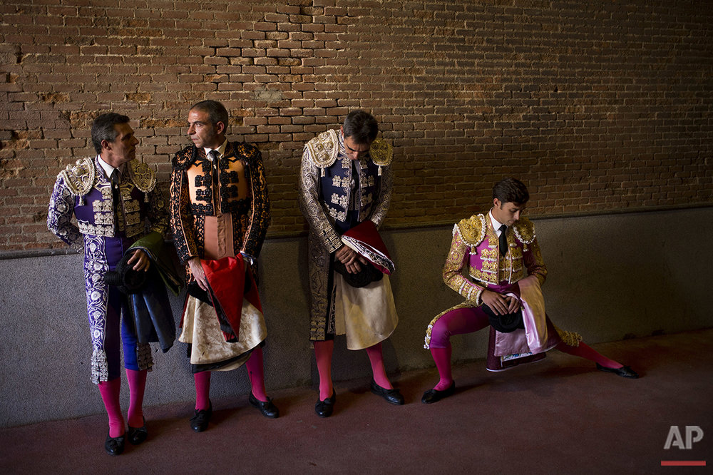 Spanish bullfighter Tulio Salguero, right, stretches next to his bullfighter assistants before entering the ring during a bullfight at the Las Ventas bullring in Madrid, Sunday, July 24, 2016. (AP Photo/Francisco Seco)