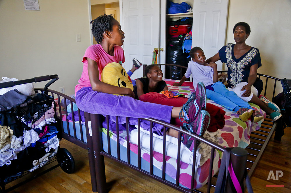 "In this Wednesday, July 20, 2016 photo, Tonia Handy, far right, and her daughters, Rainn, 10, far left, Tai, 11, second from left, and Brooke, 8, second from right, together in the bedroom of their apartment in a Brooklyn shelter, in New York. ""Some families meet at the dinner table, we have these mattresses that were put together by two twin beds and that's our meeting place,"" said Handy. ""We do everything in that bed. It's somewhere to connect."" (AP Photo/Bebeto Matthews)"
