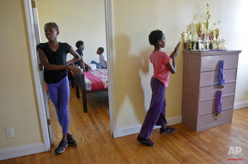 "In this Wednesday, July 20, 2016 photo, Tonia Handy, second from left, chats with her youngest daughter Brooke Sheppard, 8, second from right, while older sisters Tai Sheppard, 11, far left, and Rainn Sheppard, 10, far right, stand out side the bedroom door near a chest-of-drawer laden with trophies and medals, in New York. The sisters have only been running track and field for a year and a half, but already rank at the top of their field. ""They're some of the best athletes in the country in their age groups,"" said their coach Jean Bell of the Jeuness Track Club. ""For the upcoming junior Olympics in Houston we expect for them to bring home many, many medals and that's not an easy feat."" (AP Photo/Bebeto Matthews)"