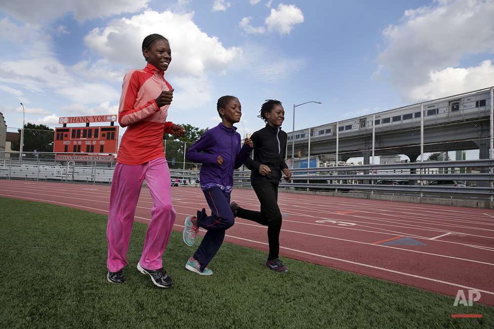 In this July 11, 2016 photo, Tai Sheppard, 11, Brooke Sheppard, 8, and Rainn Sheppard, 10, left to right, run warm-up laps at Boys and Girls High School, in the Brooklyn borough of New York. Every morning, the three young sisters wake up together with their mom in one bed in a Brooklyn homeless shelter. Every afternoon, they train in a sport that they hope will put them on a path to a better life. The girls have blossomed since taking up track and field just a year and a half ago, rising to the top tier of their national age-group rankings and earning a spot in the Junior Olympic Games, now underway in Houston. (AP Photo/Richard Drew)