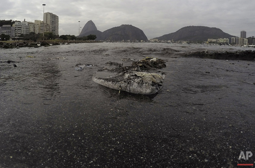 Thrash floats on the water of Botafogo beach next to the Sugar Loaf mountain and the Guanabara Bay where sailing athletes will compete during the 2016 Summer Olympics in Rio de Janeiro, Saturday, July 30, 2016. (AP Photo/Leo Correa)