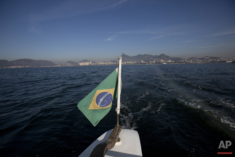 In this July 11, 2016 photo, Brazil's national flag decorates the boat used to collect water samples from Guanabara Bay for an ongoing water quality study commissioned by The Associated Press in Rio de Janeiro. The AP published the first results of its 16-month study over a year ago, showing levels of viruses that cause stomach and respiratory illnesses and more rarely heart and brain inflammation at levels up to 1.7 million times what would be considered worrisome in the United States or Europe. Since then, athletes have been taking elaborate precautions to prevent illnesses that could potentially knock them out of the competition. (AP Photo/Silvia Izquierdo)