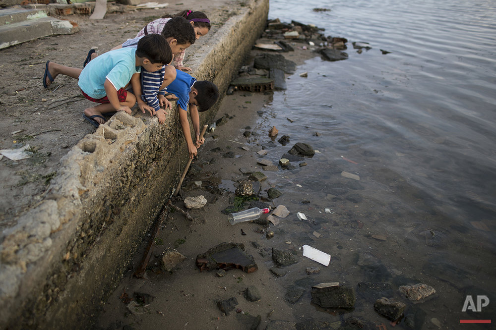 Children try to catch a crab as they play on the polluted shore of Guanabara Bay in Rio de Janeiro, Saturday, July 30, 2016. In Rio, the main tourist gateway to the country, a centuries-long sewage problem that was part of Brazil's colonial legacy has spiked in recent decades in tandem with the rural exodus that saw the metropolitan area nearly double in size since 1970. (AP Photo/Felipe Dana)