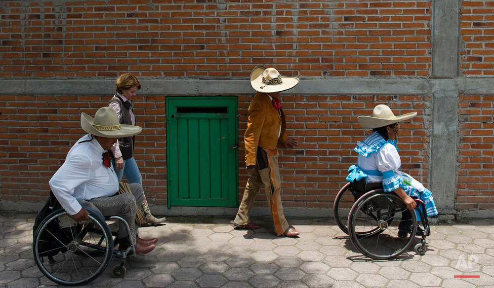 "In this July 10, 2016 photo, accompanied by Mexican cowboy and team captain Juan Manuel Garcia, Salvador Espinoza and his wife Graciela Sanchez Martinez wheel themselves to a staging area at a Mexican rodeo arena in Cuautitlán Izcalli, Mexico. ""It is a sensation that you can't explain,"" said Garcia, who survived a stroke and seven-month coma that left him with muscular weakness on the right side of his body, total loss of mobility in his right leg and three amputated fingers. ""Now it is gratifying, now it is something motivating, to know that I can dominate any animal."" (AP Photo/Nick Wagner)"