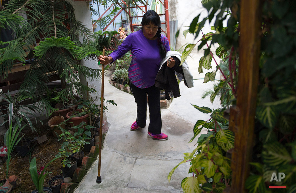 In this July 21, 2016 photo, Graciela Sanchez Martinez supports herself with a cane as she walks through her outdoor patio, in Chalco, Mexico, to a waiting van driven by her husband, Salvador Espinoza. Sanchez Martinez was diagnosed at age 2 with Guillain-Barre syndrome, a nerve disorder that can cause muscle weakness and sometimes paralysis. (AP Photo/Nick Wagner)