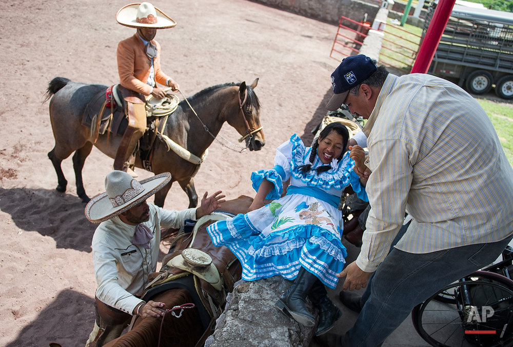 In this July 10, 2016 photo, Graciela Sanchez Martinez, a female rodeo performer known as an escaramuza, is helped from her wheelchair onto a saddled horse at the Mexican rodeo arena in Cuautitlán Izcalli, Mexico. Sanchez Martinez, who was diagnosed at age 2 with a nerve disorder that causes her muscle weakness, said she and her husband have lost count of how many times they've fallen during competition, and she joked that Paracharreria (Pararodeo) actually involves a 10th event,  trying to stay on the horse. (AP Photo/Nick Wagner)