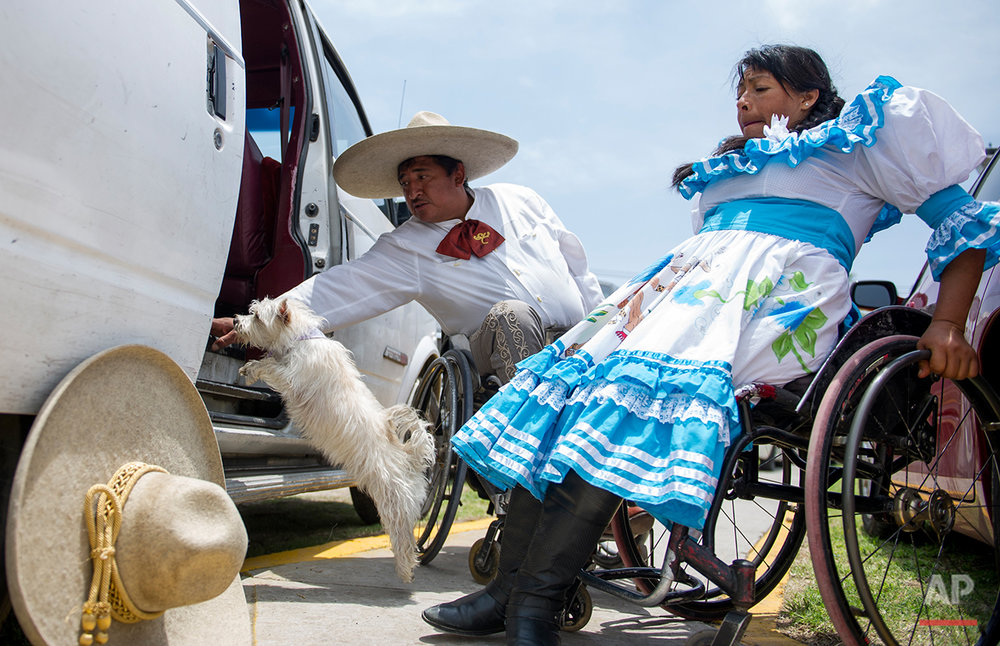 "n this July 10, 2016 photo, charro Salvador Espinoza calls for his dog Susana to hop into their van as his wife, Graciela Sanchez Martinez, dressed in her ""escaramuza"" outfit for female rodeo performers, lifts herself into her wheelchair, after arriving at a Mexican rodeo arena in Cuautitlán Izcalli, Mexico. ""This is where I have learned that athletes in wheelchairs have no limits,"" said Espinoza, who lost use of his legs 16 years ago when he fell from a four-story building while installing air conditioners. ""The only limit is the one people give themselves."" (AP Photo/Nick Wagner)"