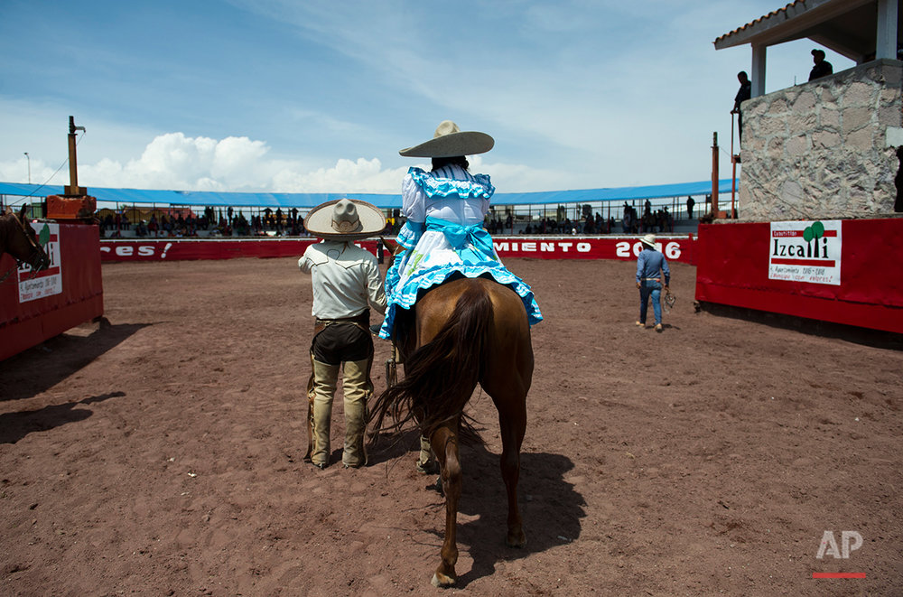 In this July 10, 2016 photo, escaramuza Graciela Sanchez Martinez enters the arena as the Queen of Paracharreria in Cuautitlán Izcalli, Mexico. Sanchez Martinez and her husband have performed in over a dozen charreadas and form the only married couple in the Patino paracharreria team. Sanchez Martinez was diagnosed at age 2 with Guillain-Barre syndrome, a nerve disorder that can cause muscle weakness and sometimes paralysis. (AP Photo/Nick Wagner)