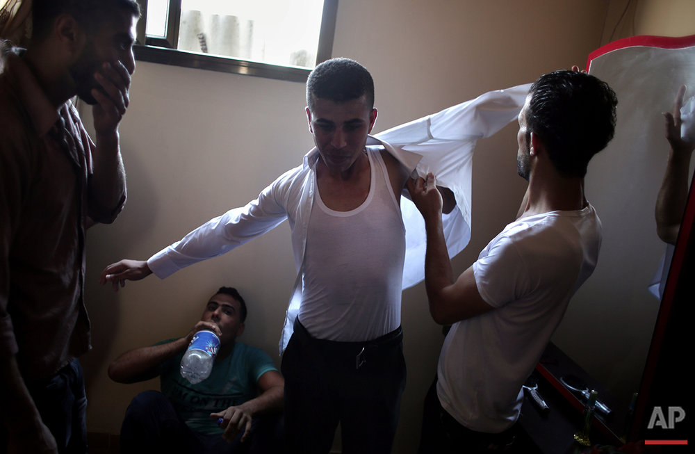 In this Saturday, July 31, 2016 photo, friends of Palestinian groom Saed Abu Aser help him wear a tuxedo in the family house as a tradition preparing him for his wedding in Gaza City. (AP Photo/ Khalil Hamra)