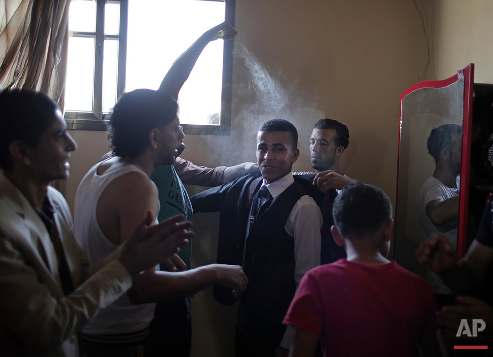 In this Saturday, July 31, 2016 photo, friends of Palestinian groom Saed Abu Aser help him wear a tuxedo in the family house as a tradition preparing him for his wedding in Gaza City. (AP Photo/Khalil Hamra)