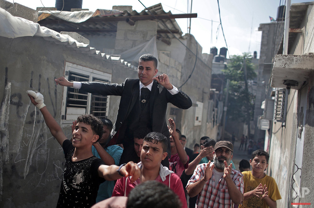 In this Saturday, July 31, 2016 photo, friends and relatives of Palestinian groom Saed Abu Aser carry him on shoulders while dancing around the neighborhood before his wedding party in Gaza City. (AP Photo/Khalil Hamra)