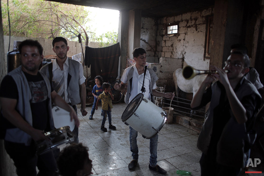 In this Saturday, July 31, 2016 photo, members of a drums band play music in the family house of Palestinian groom Saed Abu Aser as part of the preparations for his wedding party in Gaza have emerged as a welcome celebration that slices through the often morose existence in the Gaza Strip. (AP Photo/Khalil Hamra)