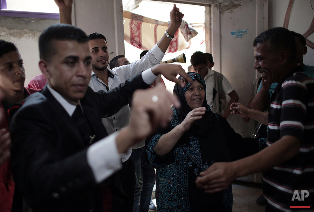 In this Saturday, July 30, 2016 photo, Palestinian groom Saed Abu Aser, second left, dances with his relatives in the family house during his wedding party, in Gaza City. (AP Photo/ Khalil Hamra)
