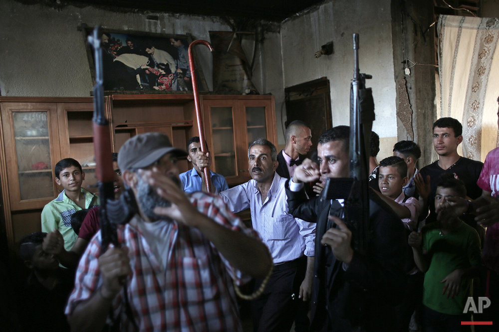 In this Saturday, July 31, 2016 photo, Palestinian groom Saed Abu Aser, right,  dance with relatives holding guns in the family house during his wedding party in Gaza City. (AP Photo/ Khalil Hamra)