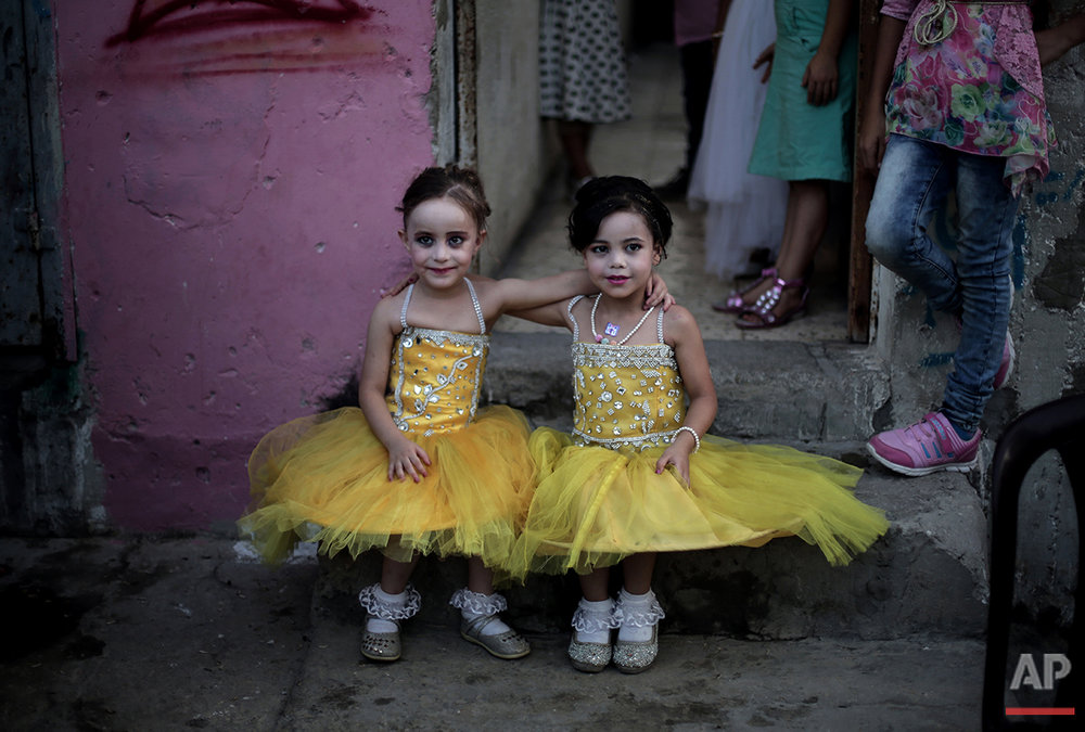 In this Saturday, July 31, 2016 photo, two dressed up girls pose for a picture as they sit in front of the family house during the wedding party of Palestinian groom Saed Abu Aser in Gaza City. (AP Photo/ Khalil Hamra)