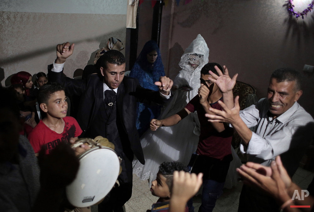 In this Saturday, July 31, 2016 photo, Palestinian groom Saed Abu Aser and relatives danc in front of his bride, Falasteen, in her family house during his wedding party in Gaza City. (AP Photo/Khalil Hamra)
