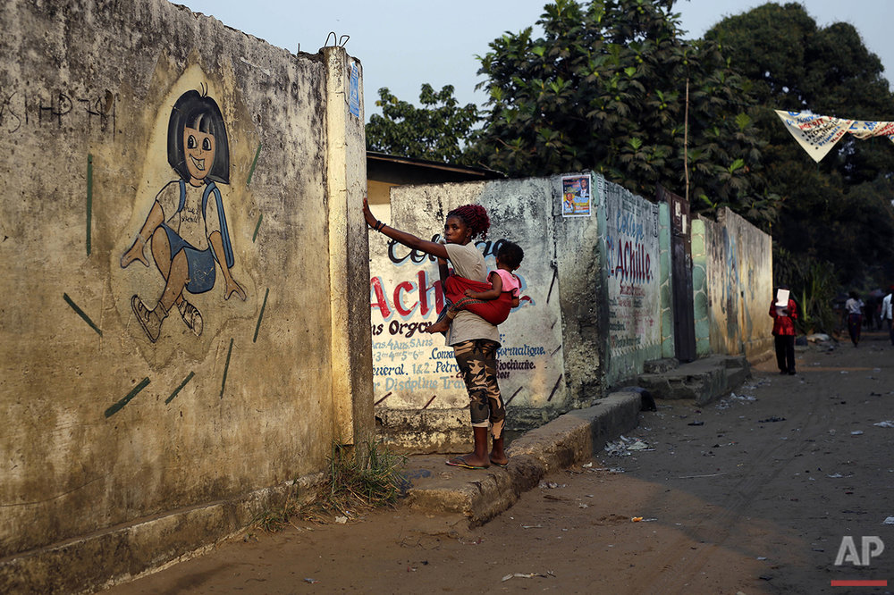 In this photo taken Wednesday July 20, 2016, residents of the Kisenso district of Kinshasa, Democratic Republic of Congo, walk by a kindergarten. (AP Photo/Jerome Delay)