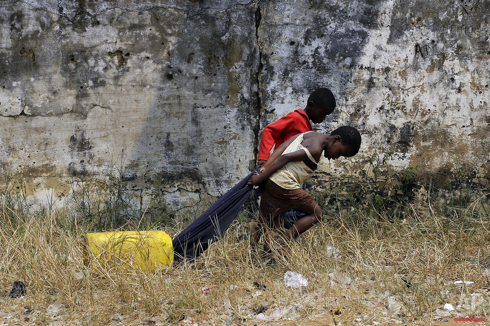 In this photo taken Wednesday July 20, 2016, children pull water in the Kisenso district of Kinshasa, Democratic Republic of Congo. (AP Photo/Jerome Delay)