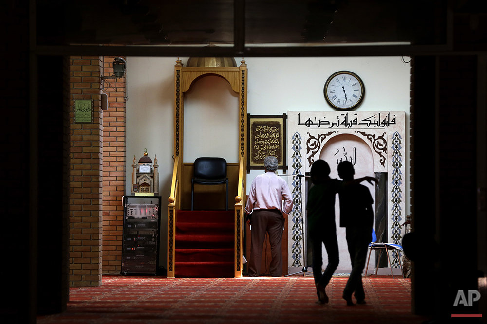 A man prays as two children walk at the Greek-Arab Cultural Center, a muslim prayer site in Athens, Thursday, Aug. 4, 2016. Lawmakers in Greece have approved construction of a state-funded mosque near central Athens, a proposal that triggered dissent within the country's coalition government amid a heated public debate on how to manage the migrant crisis. (AP Photo/Thanassis Stavrakis)