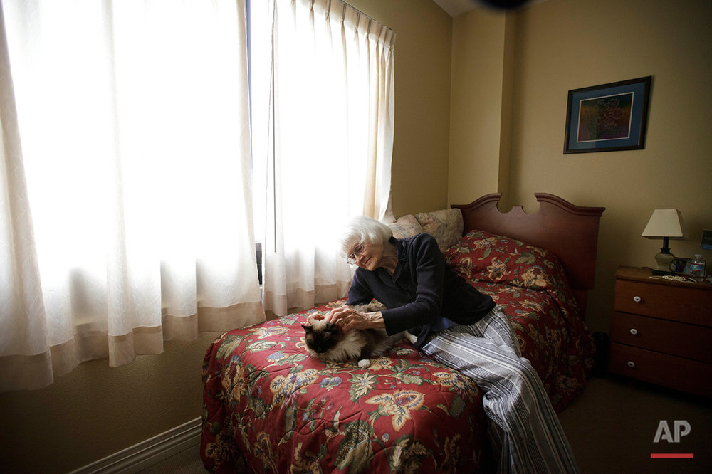 Joyce Kavanagh pets her cat as she sits in her room at the Silverado Senior Living Center Tuesday, May 1, 2012, in Encinitas, Calif. At the senior center, residents are encouraged to bring their pets. Everything from miniature horses to chinchillas  can be found on the grounds, and residents benefit from frequent contact with the pets. (AP Photo/Gregory Bull)