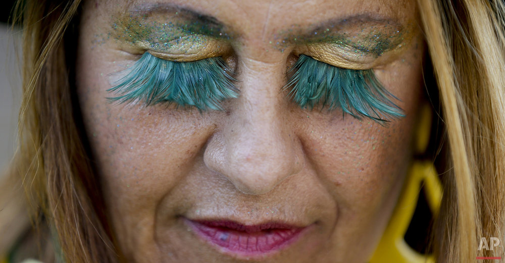 A fan from Brazil wears the national colors or her eyelashes as she lines up to enter the Maracana Stadium ahead of the opening ceremony for the 2016 Summer Olympics in Rio de Janeiro, Brazil, Friday, Aug. 5, 2016. (AP Photo/Natacha Pisarenko)
