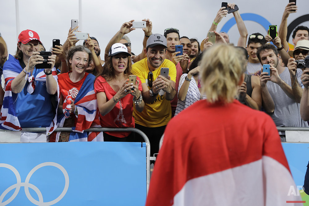 Fans photograph gold medalist Anna van der Breggen of the Netherlands, foreground, after the podium ceremony for the women's cycling road race final at the 2016 Summer Olympics in Rio de Janeiro, Brazil, Sunday, Aug. 7, 2016. (AP Photo/Patrick Semansky)