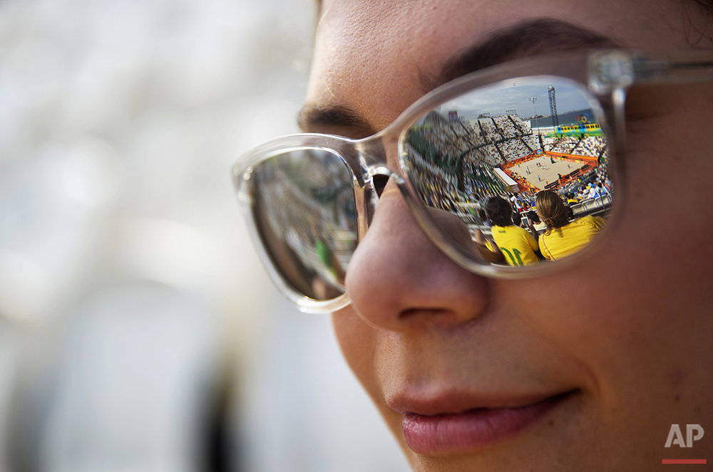 A reflection of the beach volleyball stadium is seen in the sunglasses of Ingrid Lopes, of Rio de Janeiro, as she watches a men's match between Qatar and Spain at the 2016 Summer Olympics in Rio de Janeiro, Brazil, Monday, Aug. 8, 2016. (AP Photo/David Goldman)