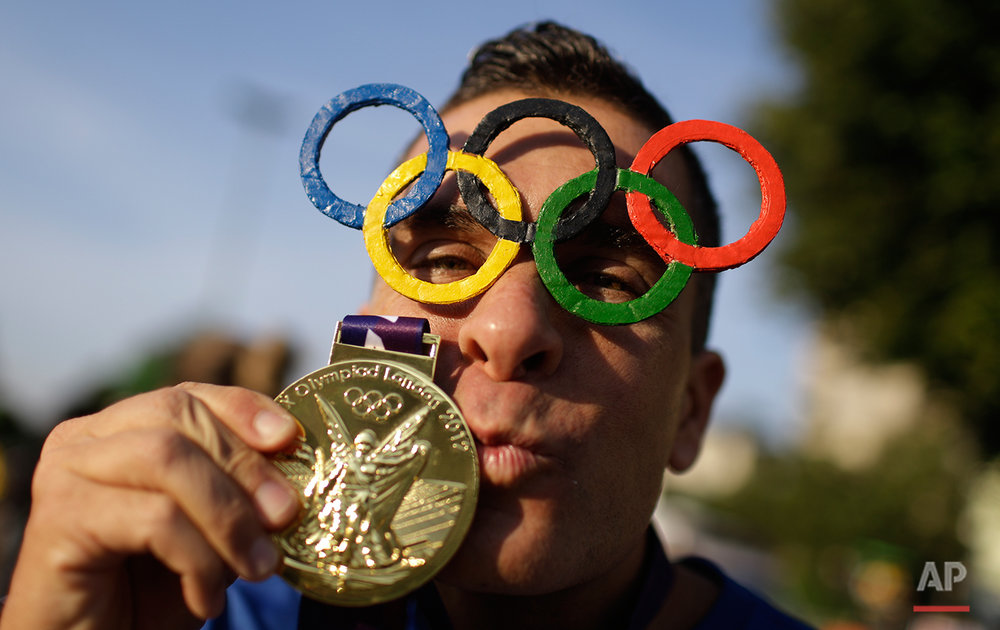 A man poses for a picture wearing Olympic rings glasses and kissing a medal before entering the Maracana Stadium ahead of the opening ceremony for the 2016 Summer Olympics in Rio de Janeiro, Brazil, Friday, Aug. 5, 2016. (AP Photo/Natacha Pisarenko)