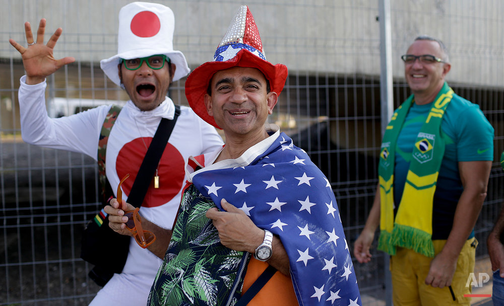 Fans from Japan, United States, and Brazil, from right to left, walk towards the Maracana Stadium ahead of the opening ceremony for the 2016 Summer Olympics in Rio de Janeiro, Brazil, Friday, Aug. 5, 2016. (AP Photo/Natacha Pisarenko)