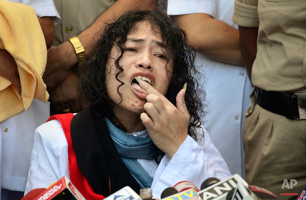 "Indian political activist Irom Sharmila licks honey from her hand to break her fast in Imphal, north-eastern Indian state of Manipur, India, Tuesday, Aug. 9, 2016. One of India's most prominent political activists ended a 16-year hunger strike Tuesday, licking honey from her hand and declaring ""I will never forget this moment."" Sharmila had been force-fed through a tube in her nose and held by police since November 2000, when she began her fast to protest a draconian security law that gives immense power to security forces in the northeastern state of Manipur. (AP Photo/Anupam Nath)"