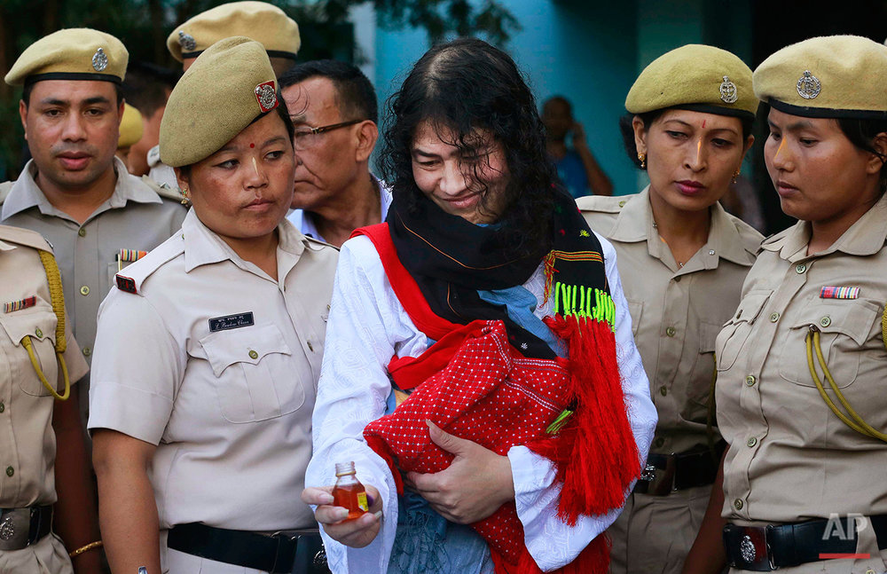 "Indian political activist Irom Sharmila picks up a bottle of honey to break her fast in Imphal, north-eastern Indian state of Manipur, India, Tuesday, Aug. 9, 2016. One of India's most prominent political activists ended a 16-year hunger strike Tuesday, licking honey from her hand and declaring ""I will never forget this moment."" Sharmila had been force-fed through a tube in her nose and held by police since November 2000, when she began her fast to protest a draconian security law that gives immense power to security forces in the northeastern state of Manipur. (AP Photo/Anupam Nath)"