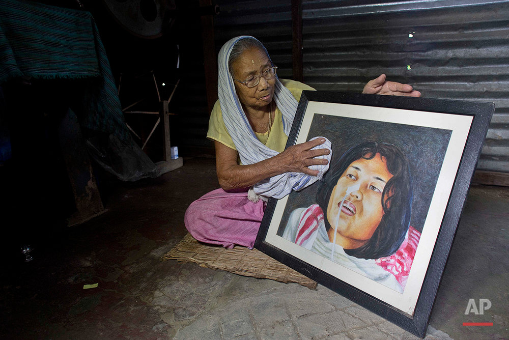 Irom Sakhi Devi, 84, mother of Indian activist Irom Sharmila, holds and cleans a portrait of her daughter as media persons interview her at her home in Imphal, northeastern Manipur state, India, Monday, Aug.8, 2016. Sharmila, the 44-year-old activist who has been on a hunger strike for nearly 16 years to protest alleged brutality by India's military is expected to end her fast on  Tuesday, Aug. 9. (AP Photo/Anupam Nath)