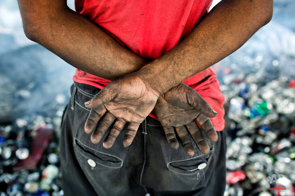 In this Aug. 3, 2016 photo, Ruhul Amin, pauses as he sorts aluminum cans on the outskirts of Dhaka, Bangladesh. A large swath of land not far from the Buriganga River is dotted with makeshift tents that are home to men and women who travel far from home to work 12 hours a day recycling cans, industrial ash and medicine blister packets into raw aluminum. The work is difficult and dangerous. The workers have no safety equipment or masks to protect themselves from the fumes and aluminum dust. (AP Photo/ A.M. Ahad)
