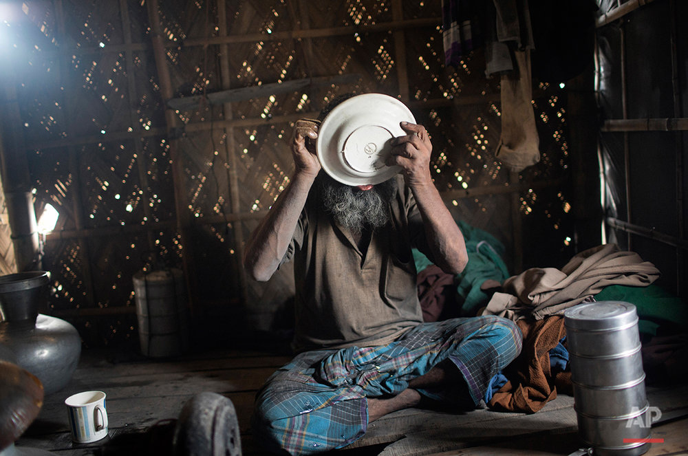 In this Aug. 6, 2016 photo, Mohammad Motaleb finishes a meal at his makeshift home near an aluminum recycling factory on the outskirts of Dhaka, Bangladesh. A large swath of land not far from the Buriganga River is dotted with makeshift tents that are home to men and women who travel far from home to work 12 hours a day recycling cans, industrial ash and medicine blister packets into raw aluminum. The work is difficult and dangerous. The workers have no safety equipment or masks to protect themselves from the fumes and aluminum dust. (AP Photo/ A.M. Ahad)