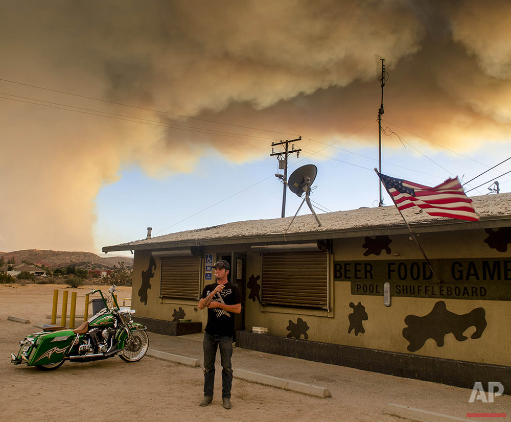Moments before evacuation, Trevor Rainwater watches a wildfire burn into Summit Valley from the Joshua Inn in Hesperia Calif., on Sunday, Aug. 7, 2016. The fire, which broke out Sunday afternoon in the San Bernardino National Forest, prompted the evacuation order of the sparsely populated Summit Valley area east of the dam. (James Quigg/The Daily Press via AP)
