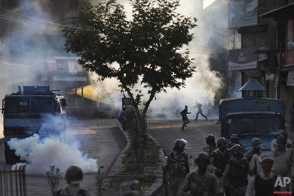 Kashmiri Muslim protesters run for cover from plumes of tear gas as Indian paramilitary soldiers walk back towards their base camp after a day-long curfew in Srinagar, Indian controlled Kashmir, Monday, Aug. 8, 2016. Kashmir has been under a security lockdown and curfew since the killing of a popular rebel commander on July 8 sparked some of the largest protests against Indian rule in recent years. (AP Photo/Dar Yasin)