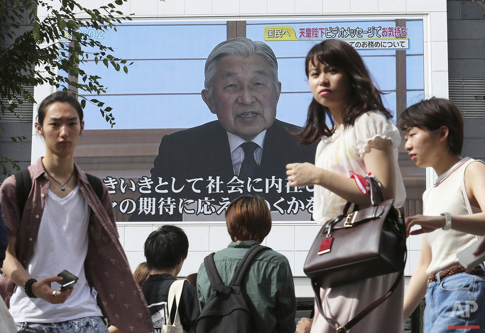 Pedestrians walk past a screen as Emperor Akihito delivers a speech in Tokyo, Monday, Aug. 8, 2016. Akihito, in a rare address to the public, signaled his apparent wish to abdicate by expressing concern about his ability to fully carry out his duties. (AP Photo/Koji Sasahara)