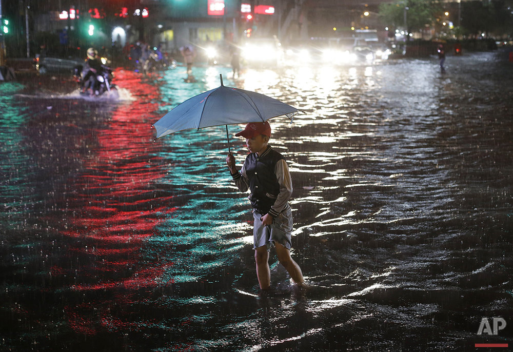 A boy crosses a flooded street during a heavy rain in Manila, Philippines on Friday, Aug. 12, 2016. Flooding snarled traffic around metropolitan Manila and stranded thousands of commuters. (AP Photo/Aaron Favila)