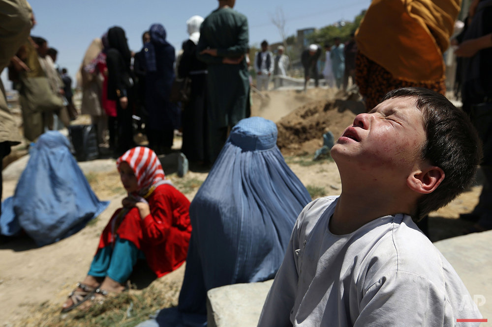The brother of Zarah, a pregnant 14-year-old who died after she was set on fire in her husband's home, sits with other mourners at her funeral in Kabul, Afghanistan, on Wednesday, Aug. 10, 2016. Zarah was allegedly tortured and set on fire by her husband's family as revenge for a marriage deal that fell through. Abuse of women and girls remains a widespread problem in the country. (AP Photos/Rahmat Gul)