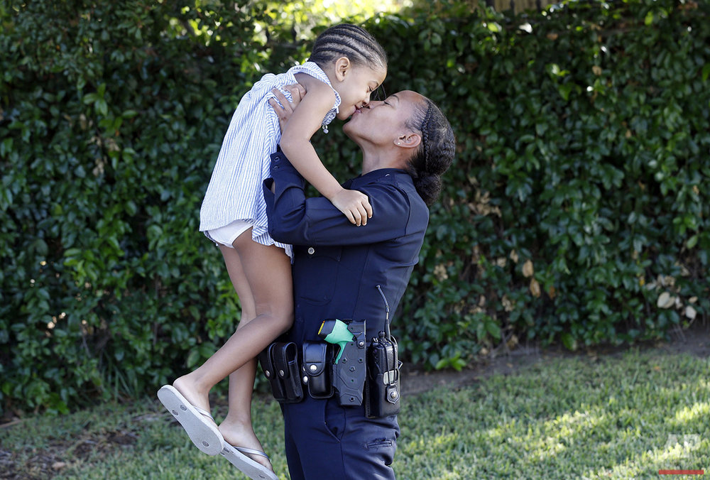 In this Thursday, Aug. 11, 2016 photo, probationary Los Angeles Police Officer Asia Hardy plays with her daughter, 4-year-old Mali Hudson, outside her home in Altadena, Calif. Hardy says she wanted to become a police officer and patrol one of the most dangerous neighborhoods in Los Angeles to serve as an example to other black people. (AP Photo/Nick Ut)