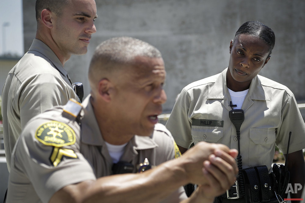 "In this Tuesday, July 19, 2016 photo, Los Angeles County sheriff's deputy recruit Renata Phillip, right, listens to recruit training officer Sean Essex at the Biscailuz Regional Training Center in Monterey Park, Calif. Phillip hopes to be an example to those who have never dealt with a black law enforcement officer. ""If I can have a positive experience with someone and maybe help them change their mind, why not?,"" she said. (AP Photo/Jae C. Hong)"