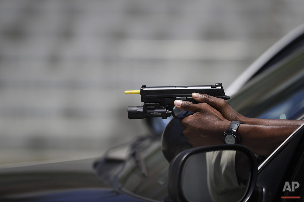 In this Tuesday, July 19, 2016 photo, Los Angeles County sheriff's deputy recruit Renata Phillip draws a weapon during her training at the Biscailuz Regional Training Center in Monterey Park, Calif. (AP Photo/Jae C. Hong)