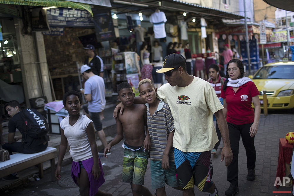 Ricardo Ramos, right, founder of Rocinha Surf School, walk with children from his surf school in the Rocinha slum in Rio de Janeiro, Brazil, Saturday, Aug. 13, 2016. (AP Photo/Felipe Dana)