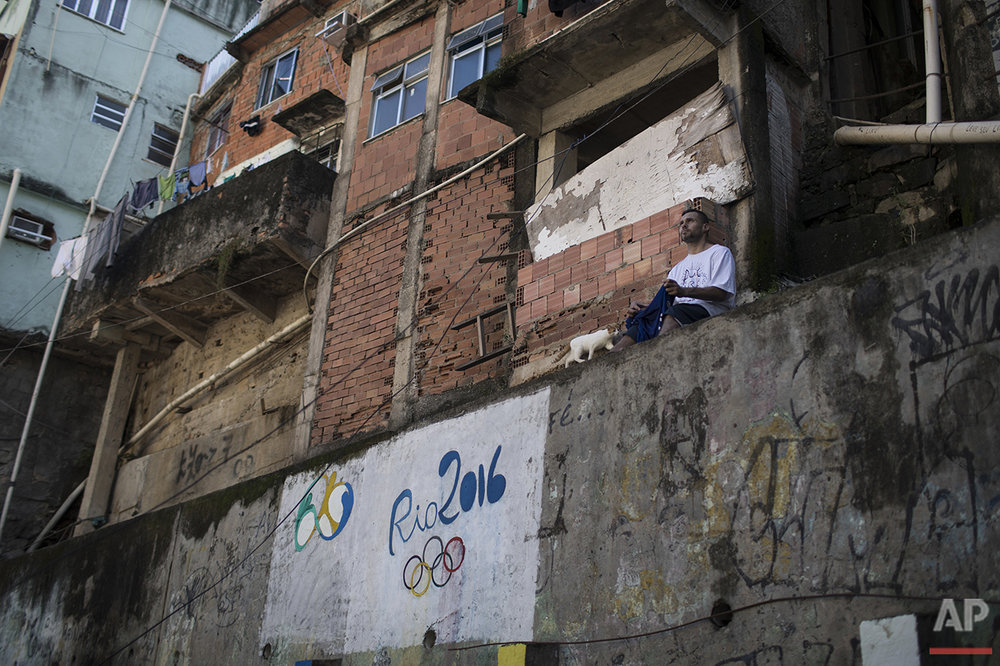 Fagner Lopes poses for a photo next to a Rio 2016 Olympics graffiti at the Rocinha slum in the nearby Sao Conrado beach in Rio de Janeiro, Brazil, Saturday, Aug. 13, 2016. (AP Photo/Felipe Dana)