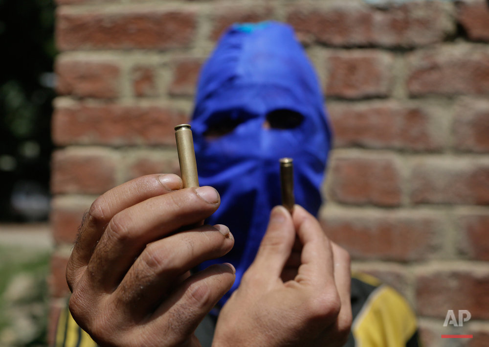 A masked Kashmiri youth shows empty bullet cartridges allegedly fired by government forces during a joint funeral of four civilians at Aripanthan village, west of Srinagar, Indian controlled Kashmir, Tuesday, Aug.16, 2016. Government forces in Indian-controlled Kashmir shot and killed four civilians and injured at least 15 others Tuesday as clashes intensified with anti-India protesters in the troubled region, police said. (AP Photo/Mukhtar Khan)