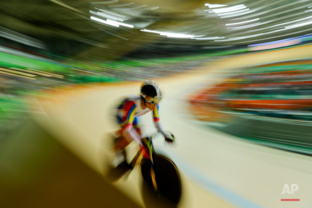 In this photo taken with slow shutter speed, Angie Sabrina Gonzalez of Venezuela competes in the women's omnium cycling flying lap at the Rio Olympic Velodrome during the 2016 Summer Olympics in Rio de Janeiro, Brazil, Tuesday, Aug. 16, 2016. (AP Photo/Pavel Golovkin)