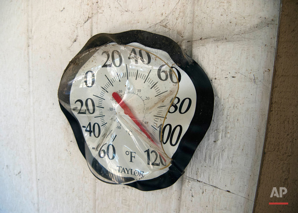 A partially melted thermometer is seen on a house that survived after a fire tore through Lower Lake, Calif., Tuesday, Aug. 16, 2016. A California man was arrested Monday on arson charges for allegedly sparking a wildfire that exploded over the weekend, destroying homes, business and other structures in the Northern California town, authorities said. (AP Photo/Josh Edelson)