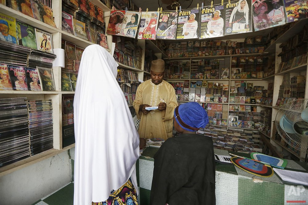 In this photo taken Sunday, April 3, 2016, Suleiman Maharazu, centre, the owner of Maharazu Bookshop, sells books to young girls in his shop in Kano, Nigeria. In the local market, stalls are signs of a feminist revolution with piles of poorly printed books by women, as part of a flourishing literary movement centered in the ancient city of Kano, that advocate against conservative Muslim traditions such as child marriage and quick divorces. Dozens of young women are rebelling through romance novels, many hand-written in the Hausa language, and the romances now run into thousands of titles. (AP Photo/Sunday Alamba)