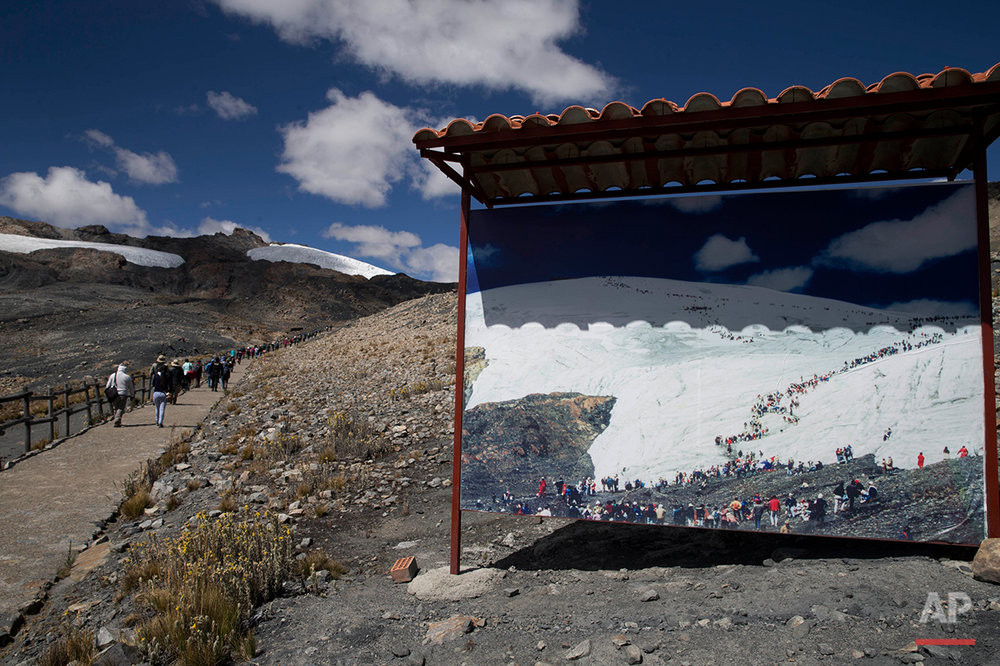 "In this Aug. 12, 2016 photo, a group of tourists walk past a photo featuring an image of the Pastoruri glacier before its retreat, during a tour called ""The Route of Climate Change"" in Huaraz, Peru. Benjamin Morales Arnao, the head of Peru's National Institute for Glacier Research, said that while the country's glaciers ""are a source of life, due to their water resources and biodiversity ... these glaciers are also a source of glacier glacial catastrophes."" (AP Photo/Martin Mejia)"